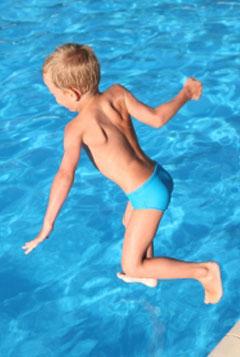 Niño que se baña en la piscina después de una sesión de logopedia a domicilio
